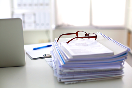 stack of papers: Laptop with stack of folders on table on white background.