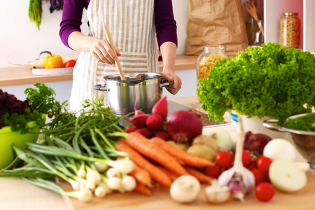 tasting: Young Woman Cooking in the kitchen. Healthy Food. Stock Photo