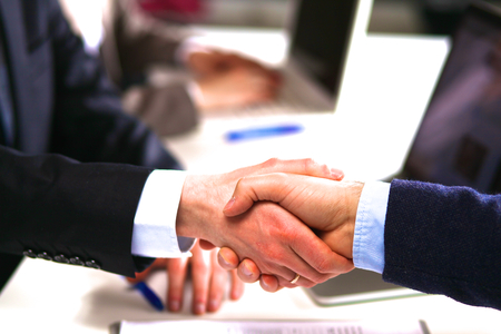 relationship strategy: Business people handshake, sitting at the table.