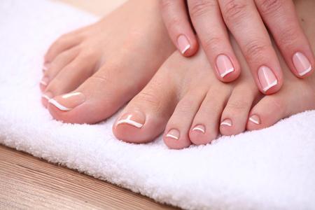 manos y pies: Foto de cerca de un hermoso pies femeninos con pedicure rojo aislado en blanco.