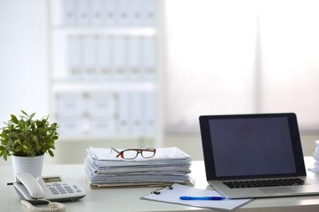 administracion de empresas: Ordenador portátil con pila de carpetas en la mesa sobre fondo blanco. Foto de archivo