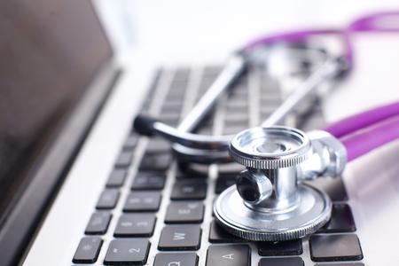 A medical stethoscope near a laptop on a wooden table, on white. Reklamní fotografie