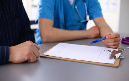 close up of patient and doctor taking notes.
