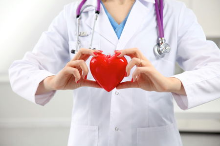 estetoscopio: Doctor con el estetoscopio examinar el coraz�n rojo. Foto de archivo