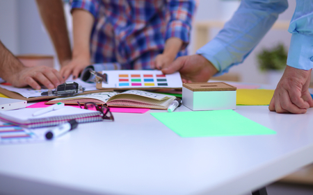 Close-up of three young creative designers working on project together. Team work.