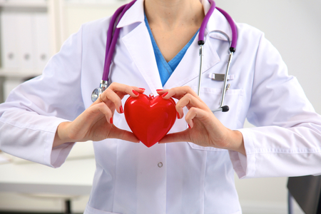 glass heart: Young woman doctor holding a red heart, in office.