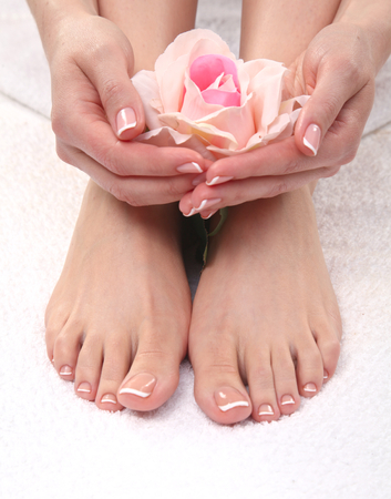 Closeup photo of a beautiful female feet with red pedicure isolated on white.