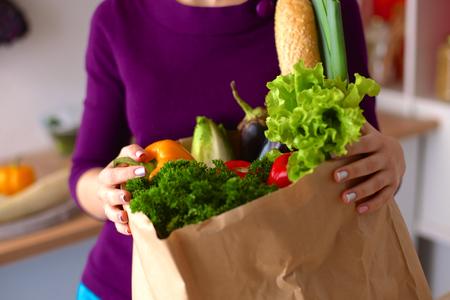 건강 한 긍정적 인 행복 한 여자 과일 및 야채의 전체 종이 쇼핑 가방을 들고.