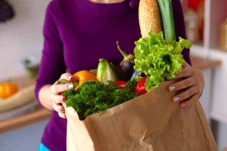 woman shopping cart: Healthy positive happy woman holding a paper shopping bag full of fruit and vegetables.
