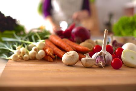 �cooking: Mujer joven que cocina en la cocina. Comida saludable.