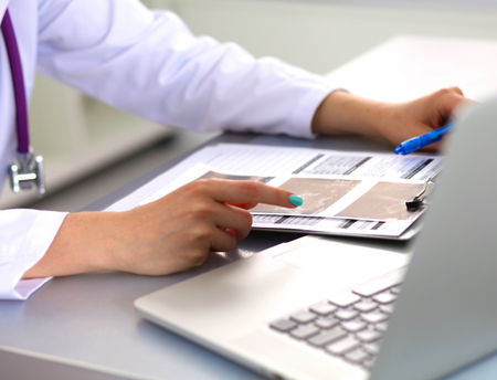 Portrait de jeune femme médecin en blouse blanche à l'ordinateur.