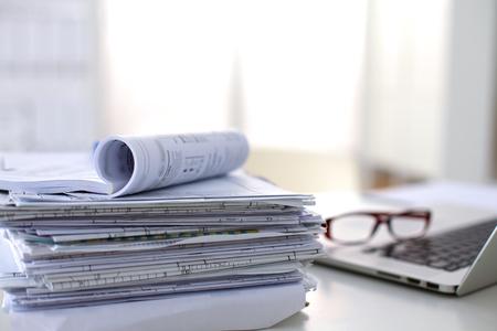 folder: Ordenador portátil con pila de carpetas en la mesa sobre fondo blanco. Foto de archivo