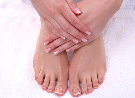 foot spa: Closeup photo of a beautiful female feet with red pedicure isolated on white.