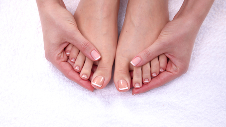 woman foot: Closeup photo of a beautiful female feet with red pedicure isolated on white.