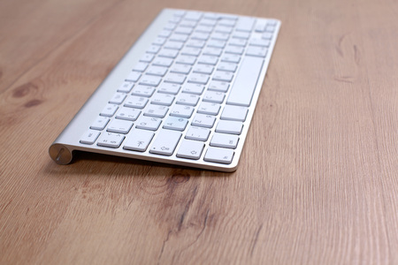 inputting: computer keyboard lying on a wooden table. Stock Photo