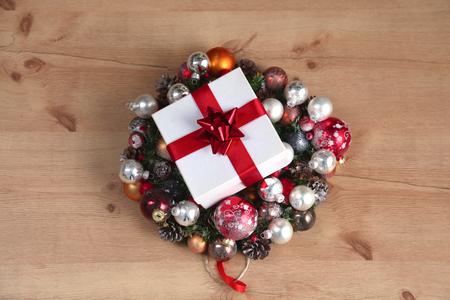 coronas navidenas: a gift lying on the Christmas wreaths on the wooden table. Foto de archivo