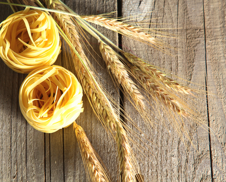 italian cusine: Raw homemade pasta and ingredients for pasta on wooden background.