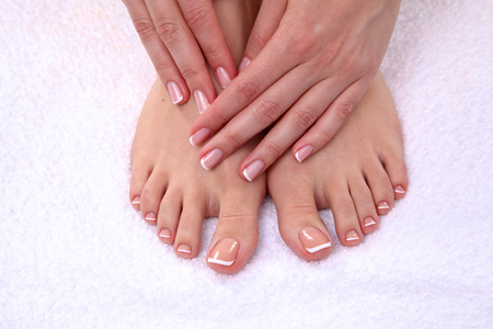 french pedicure: Closeup photo of a beautiful female feet with red pedicure.