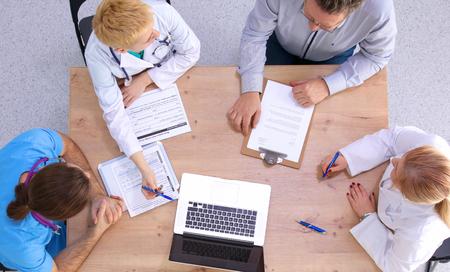 grupo de médicos: Médicos y médicas que trabajan en los informes en la oficina médica.