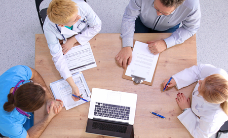 group of workers: Male and female doctors working on reports in medical office. Stock Photo