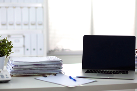 pile of documents: Laptop with stack of folders on table on white background.