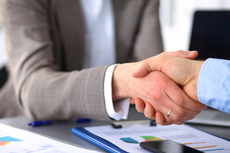 businessmen handshake: Business handshake. Two businessman shaking hands with each other in the office.