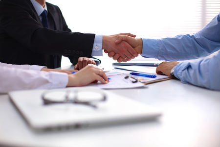 business suit: Business handshake. Two businessman shaking hands with each other in the office.