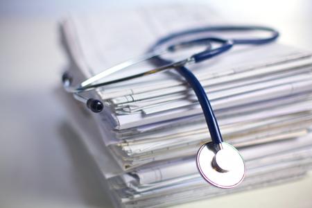 equipos medicos: libros archivo de carpeta y un estetoscopio aislados sobre fondo blanco.