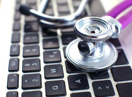 teclado de ordenador: Un estetoscopio médico cerca de una computadora portátil en una mesa de madera, sobre fondo blanco. Foto de archivo