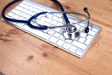 red stethoscope: A medical stethoscope near a laptop on a wooden table, on white. Stock Photo