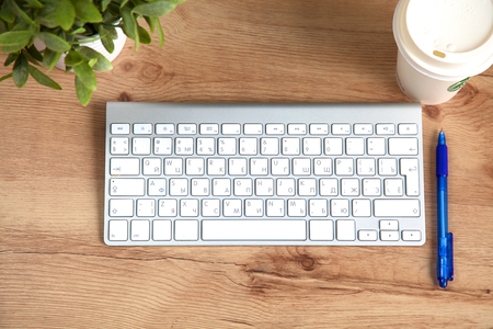 internet keyboard: Modern aluminum keyboard on the wooden table in the office. Stock Photo