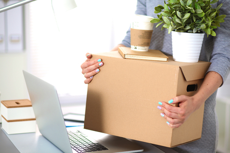 moving box: Happy team of businesspeople moving office, packing boxes, smiling.