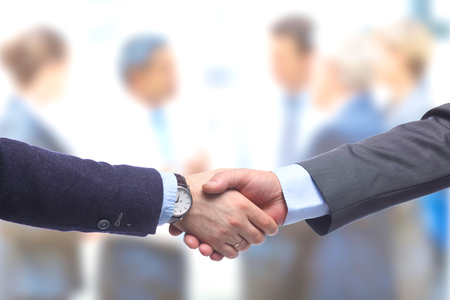 stretta di mano: Business handshake. Two businessman shaking hands with each other in the office.