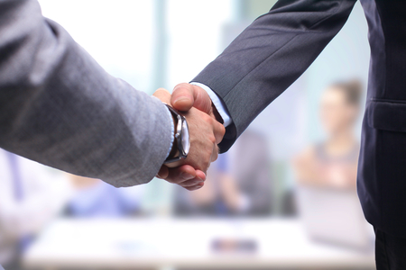 apreton de mano: Negocios apretón de manos. Dos hombre de negocios dándose la mano unos con otros en la oficina. Foto de archivo