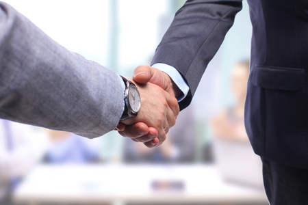 to trust: Business handshake. Two businessman shaking hands with each other in the office.
