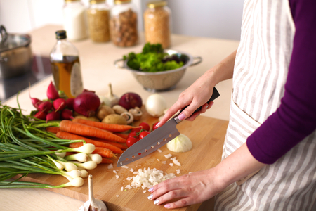 cooking: Young Woman Cooking in the kitchen. Healthy Food. Stock Photo