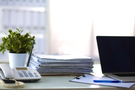 Laptop with stack of folders on table on white background. Stock Photo