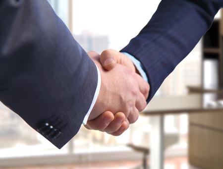 dando la mano: Negocios apretón de manos. Dos hombre de negocios dándose la mano unos con otros en la oficina. Foto de archivo