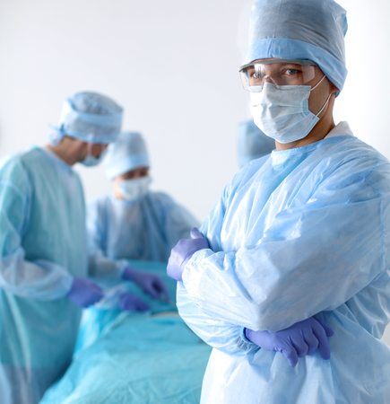 Team of surgeon in uniform perform operation on a patient at cardiac surgery clinic.