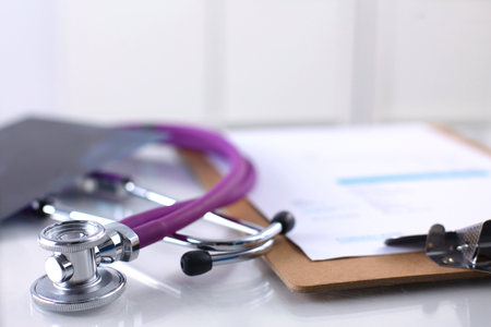 medical career: A medical stethoscope near a laptop on a wooden table, on white. Stock Photo
