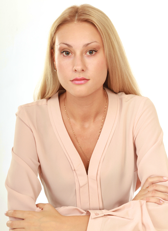 leaning on elbows: Beauty girl portrait. Young natural woman with clean face sitting at white table leaning on her elbows, over white background.