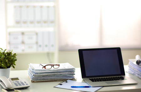 business supplies: Office table with blank notepad and laptop .