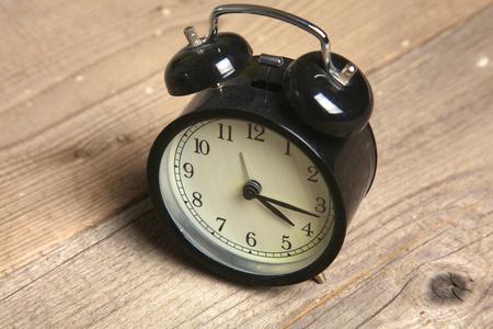 alarmclock: Retro alarm clock standing on vintage table. Stock Photo