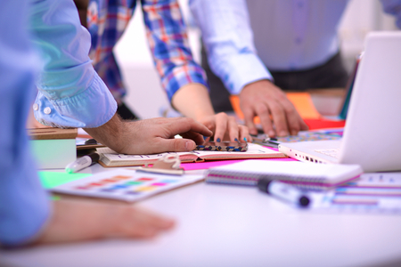 Close-up de trois jeunes designers créatifs qui travaillent sur le projet ensemble. Le travail d'équipe. Banque d'images