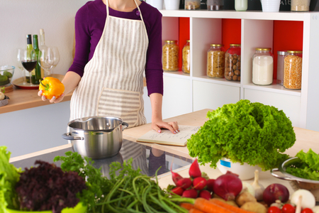woman cooking: Young Woman Cooking in the kitchen. Healthy Food. Stock Photo