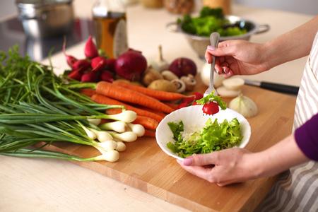 personas saludables: Mujer joven que cocina en la cocina. Comida saludable.
