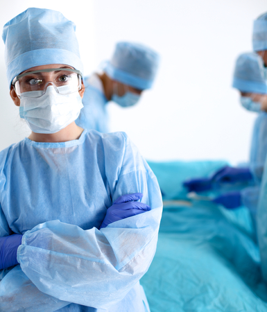 surgeon: Team of surgeon in uniform perform operation on a patient at cardiac surgery clinic.