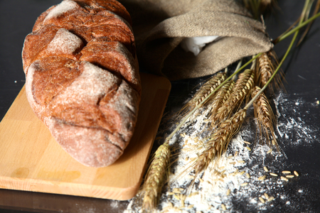 crusty: rustic crusty bread and wheat ears on a dark wooden table.