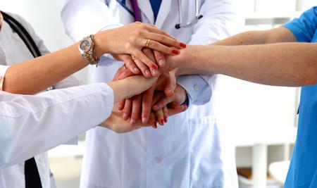 Lékaři a sestry ve zdravotnickém týmu stohují ruce.