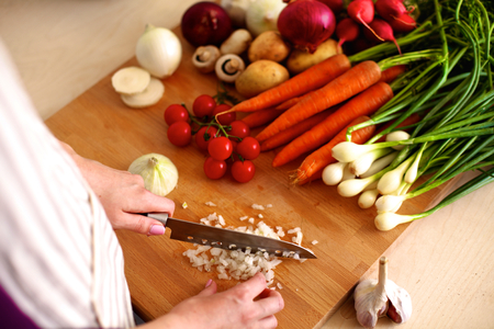 cutting vegetables: Young woman cutting vegetables in the kitchen. Stock Photo